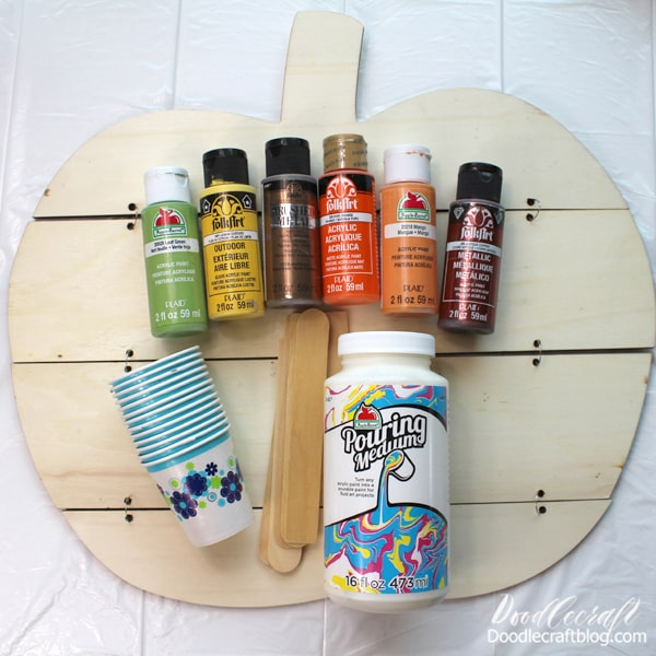 Supplies Needed for Pumpkin Paint Pour: Pumpkin Wood Cut Out  Acrylic Craft Paint  Pouring Medium  Small Paper Cups  Large Mixing Cup  Stirring Sticks  Plastic Tablecloth or garbage bag