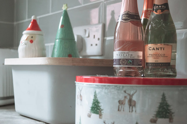 Close up of a Christmas tin, prosecco mini bottles and Christmas egg cups