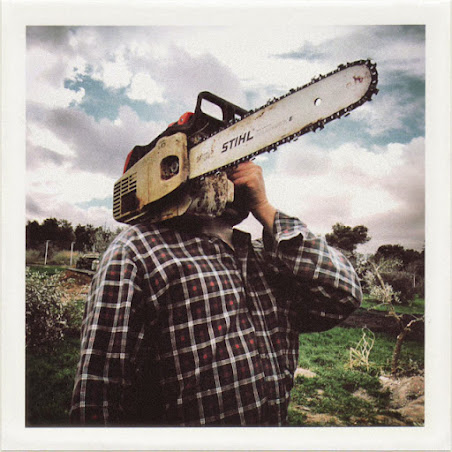 dirty photos - time - cretan landscape photo of man holding a chainsaw