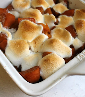 corner of pan filled with candied sweet potatoes topped with golden brown marshmallows