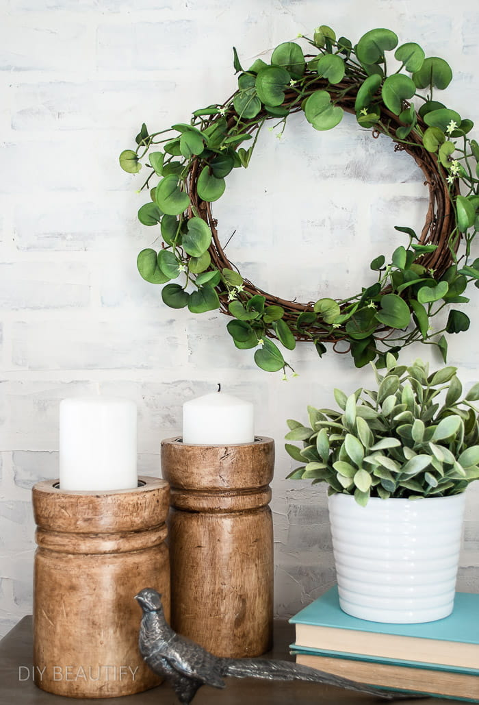 greenery wreath with wood candle holders