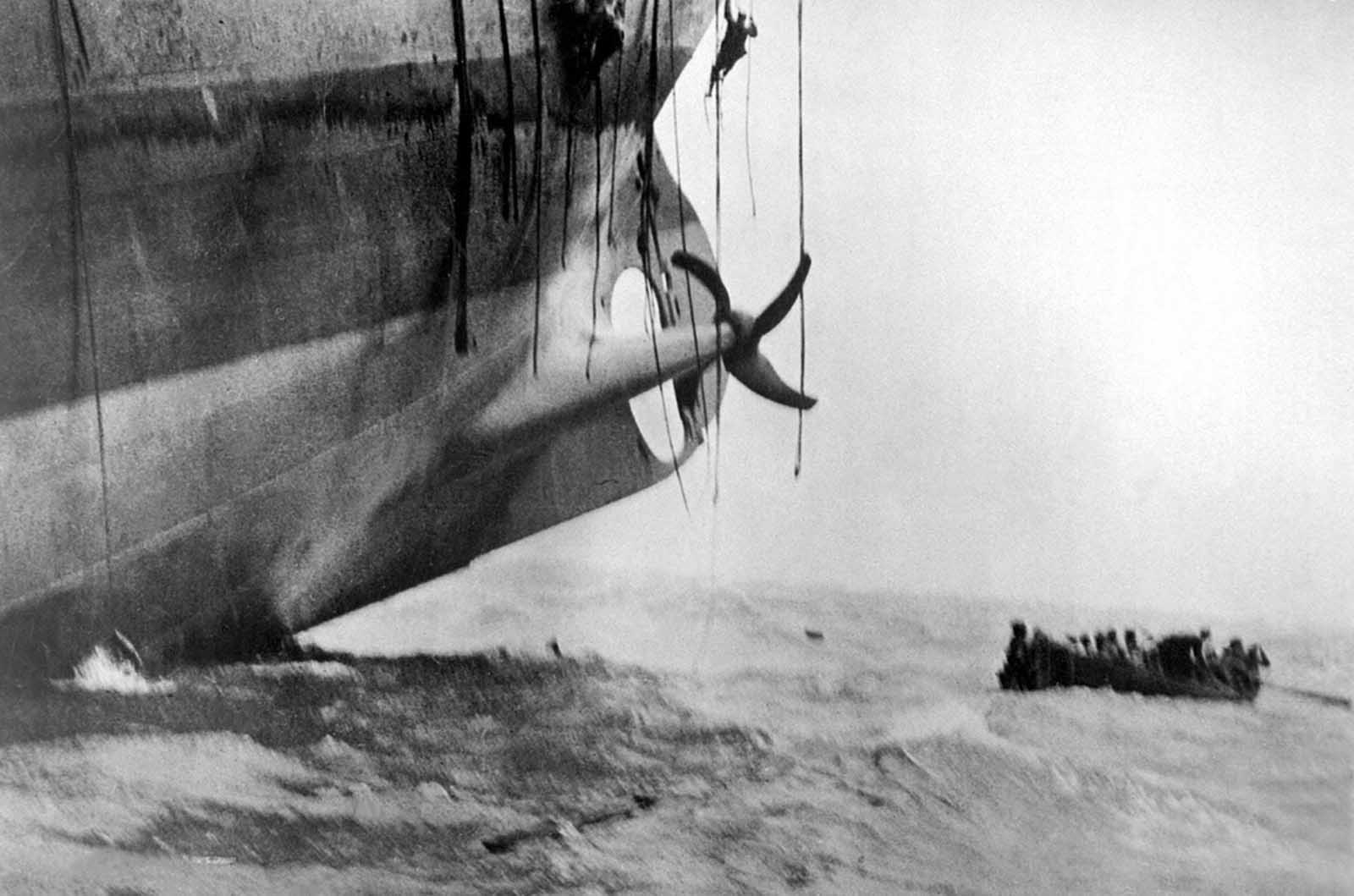 Last minute escape from a vessel torpedoed by a German sub. The vessel has already sunk its bow into the waves, and her stern is slowly lifting out of the water. Men can be seen sliding down ropes as the last boat is pulling away. Ca. 1917.