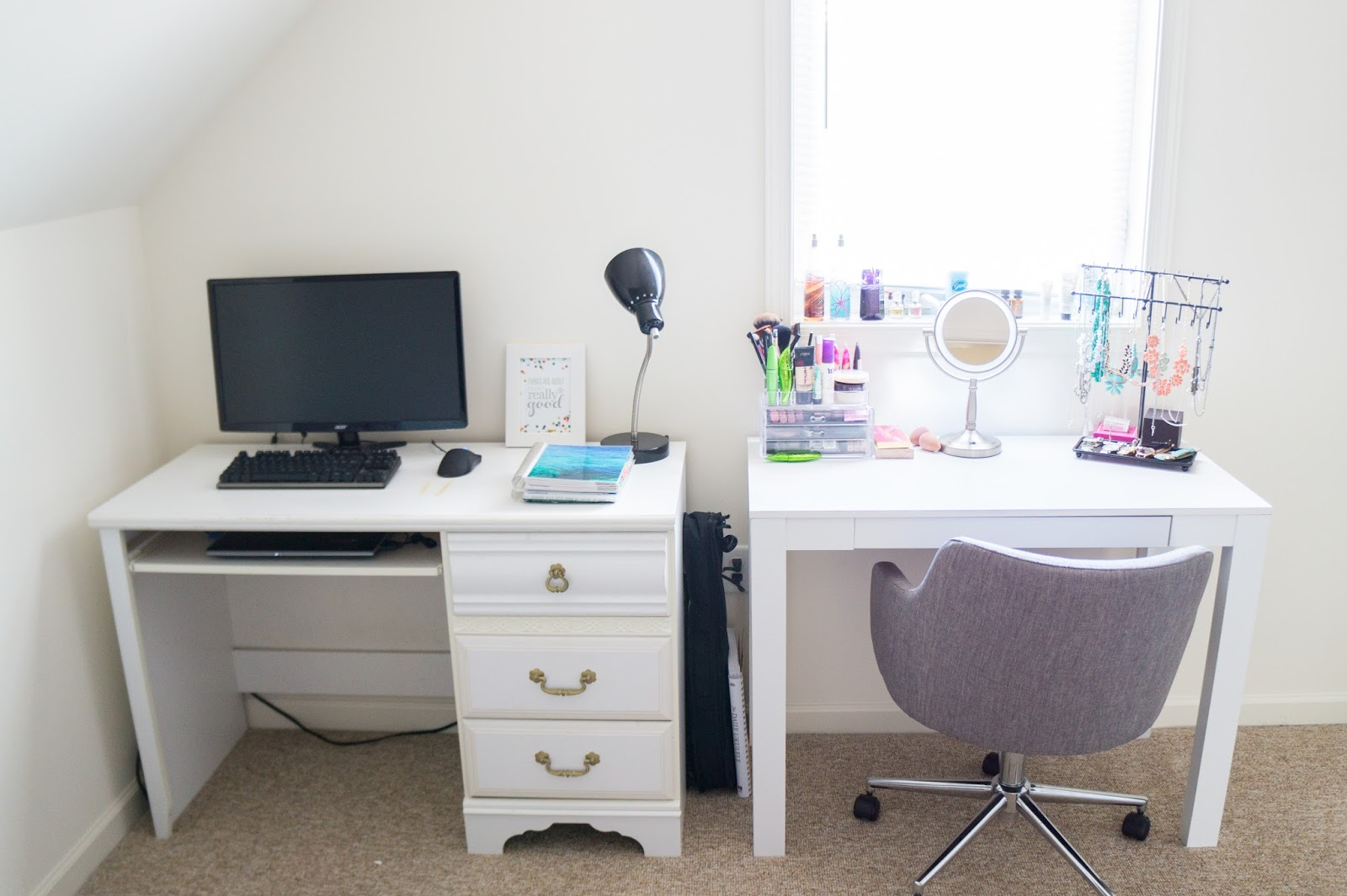 White desk with a desktop computer and a vanity next to it.