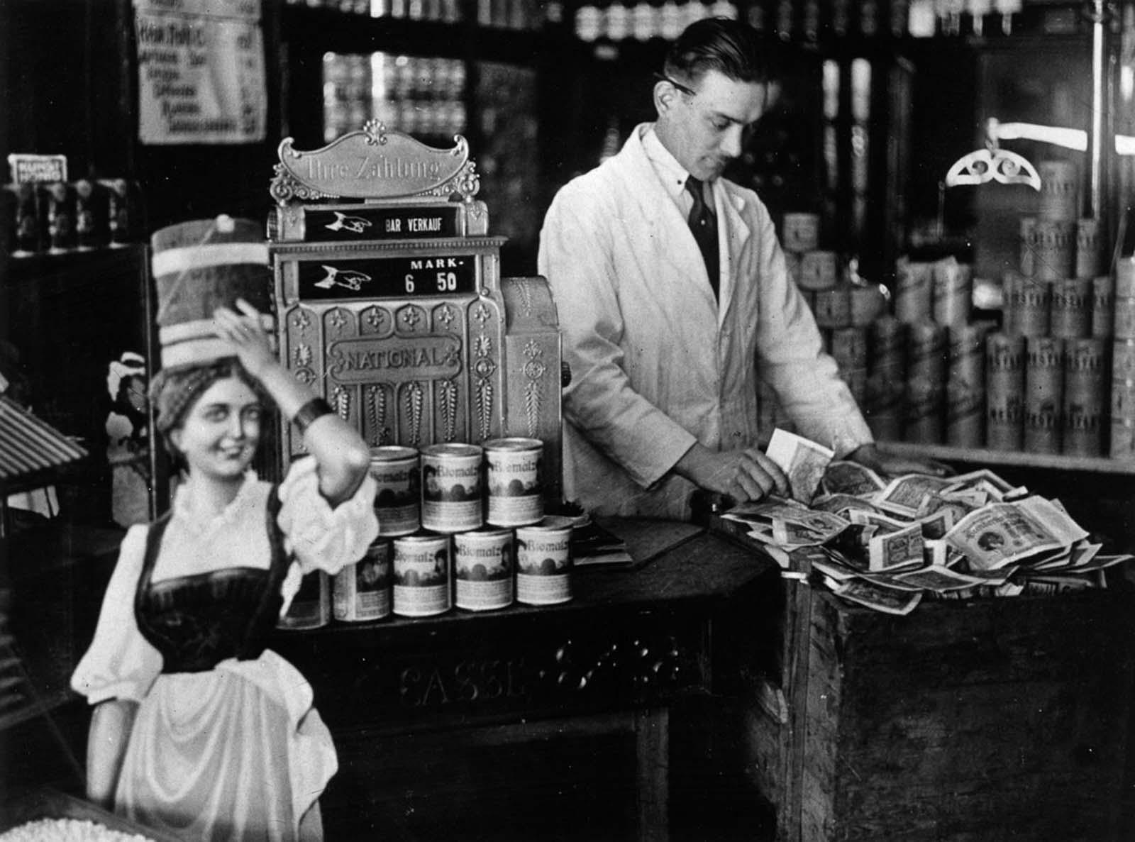 Un comerciante mete el exceso de efectivo en un cofre de té junto a su registro. 1922.