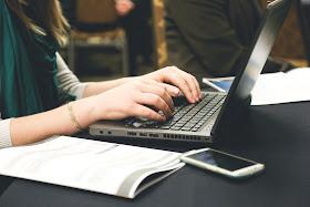 mulher com blusa branca e verde digitando no computador