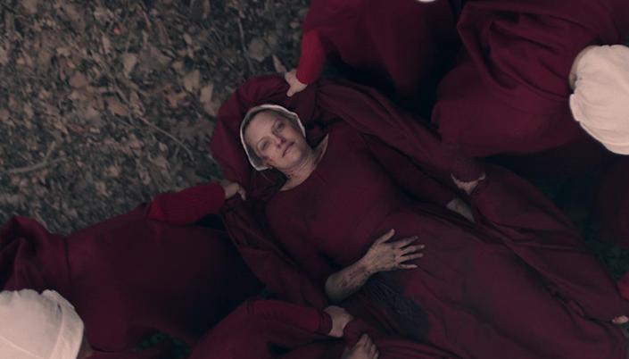 O fundo é um chão de uma floresta e várias mulheres vestidas com capas vermelhas e chapéus brancos carregam uma mulher que está no centro deitada num lençol vermelho. E essa mulher está com a mão na barriga e está toda machucada, ela sorri, ela é branca e tem o cabelo loiro e usa um chapéu branco também.