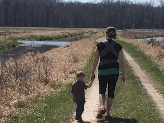 Mom walking with kids at sunny nature preserve