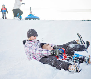 a blonde woman and a young boy lean back together on a sled in Yankton, South Dakota