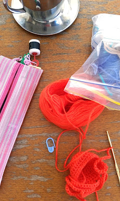 View of workbench from above. Top left corner is a silver teacup and saucer, bottom left a pink and white striped zippered case with a row counter and stitch markers attached. Right hand side has a snap-lock bag with purple-blue acrylic yarn. Bottom centre is a gold anodised steel hook in a piece of rounded crochet fabric. The tangerine orange yarn is in a skein in the centre. A blue stitch marker is resting on the bench between the skein and the work.