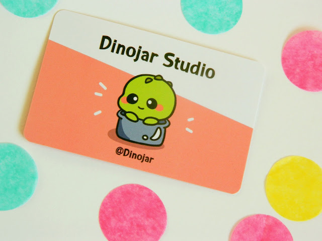 A photo of a business card for Dinojar Studios. The background is white and peach in colour and there is a little green dinosaur sitting in a jar