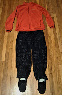 A photo of an orange Columbia sweatshirt, Star Wars pajama pants, and slippers laid out on the floor as if a human outline.