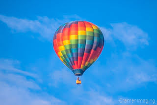 Cramer Imaging's fine art photograph of one colorful rainbow hot air balloon taking flight in Panguitch Utah with a blue morning sky