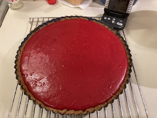 Undecorated cranberry curd tart, cooling on rack