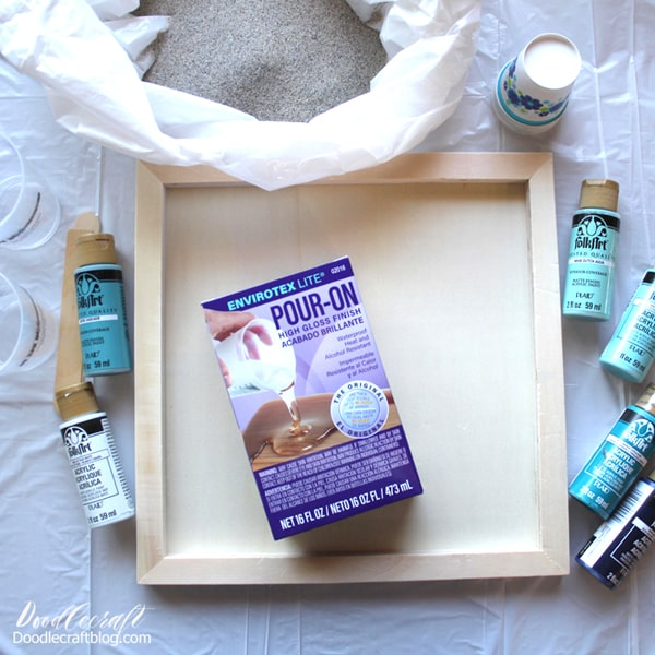 Supplies needed for ocean resin paint pour: Wood canvas, envirotex lite pour on high gloss resin, acrylic craft paint, mixing cups, stirring sticks, and beach sand.