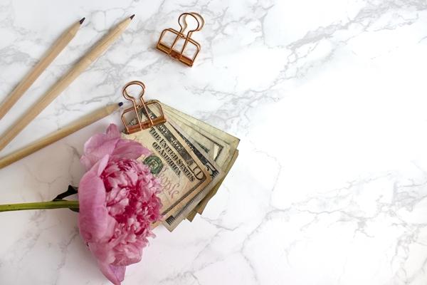 Notas de dinheiro pregadas em um clips com uma flor rosa e lápis em volta