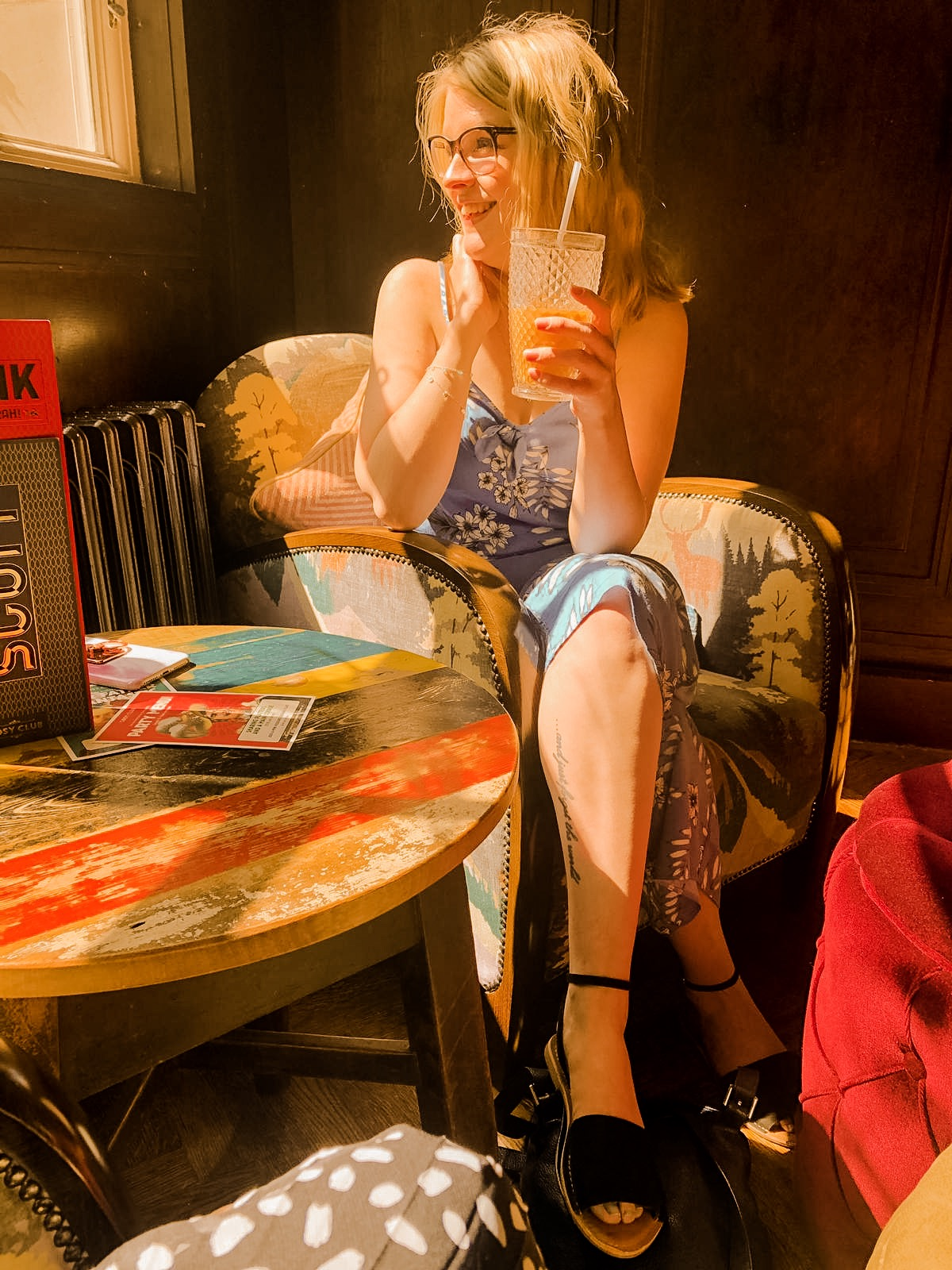 Girl in sunny window of coffee shop drinking iced latte - poetry blog post