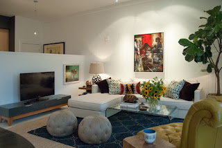 Eclectic Living room with Long Modern Sofa Bed and a Clear Glass Table on the Dark Carpet