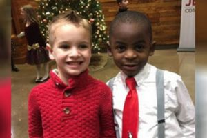 Photo of two little boys - one white and one black with matching haircuts