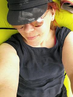 Das Fot zeigt mich mit Käptn-Mütze mit Kreidespuren darauf, Sonnenbrille, fröhlichem Gesichtsausdruck und blauem Leinenkleid.