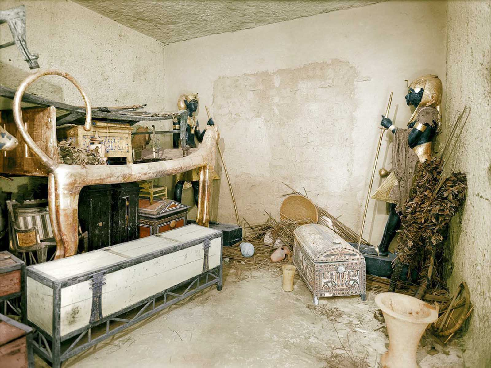 A gilded lion bed, clothes chest and other objects in the antechamber. The wall of the burial chamber is guarded by statues.