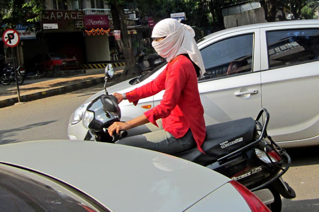 girl with white scarf and mask on scooter