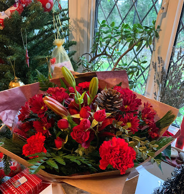 A bouquet of flowers in Christmas colours - red and gold.