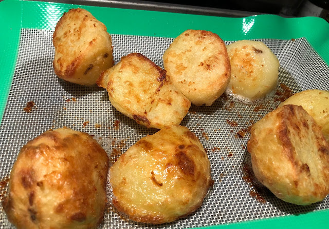 Close up of crispy roast potatoes on a silicone baking sheet