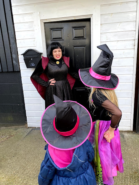 2 children dressed as witches outside a black door being guarded by a female vampire