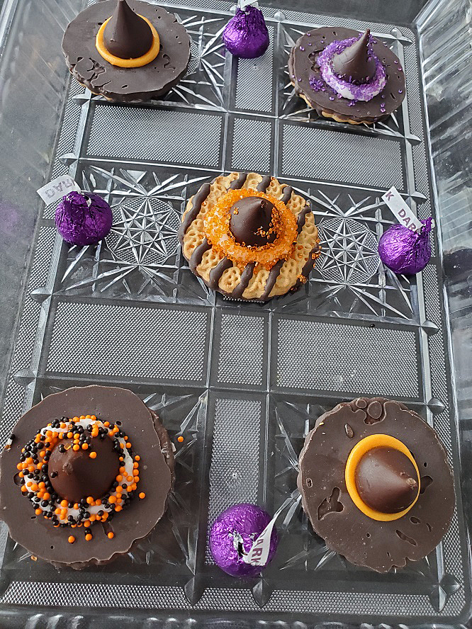 these are fudge striped cookies decorated into witch hats using orange frosting and Hersey kisses