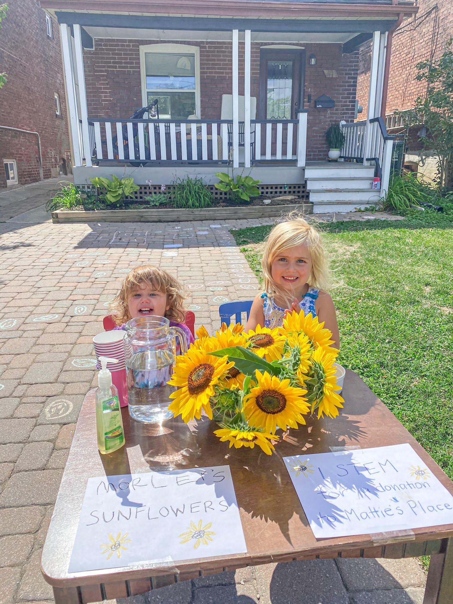 girls selling sunflowers