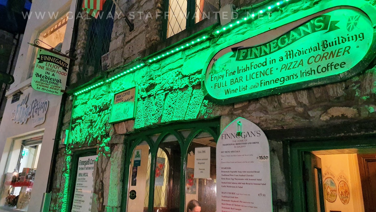Stone-fronted medieval restaurant building with green fluro lighting illuminating the signage and stonework