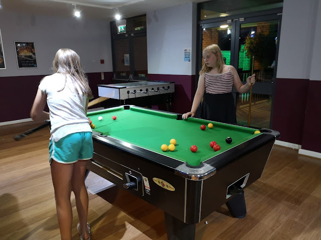 Tween girls playing pool