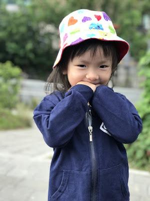 فتاة صينية صغيرة تبتسم وترتدي قبعة