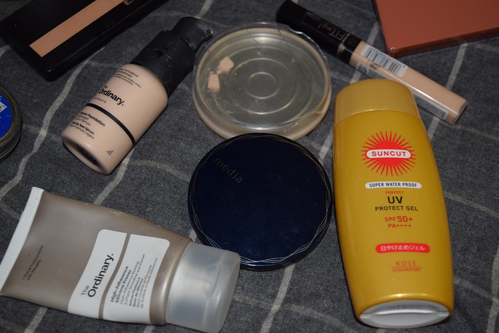 flatlay of well used makeup products on a sheet