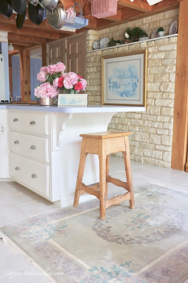 Romantic French country pink peonies on kitchen island in post and beam house with limestone wall
