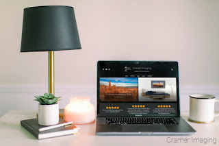 Photograph of a desk surface with the Cramer Imaging website up on a laptop screen