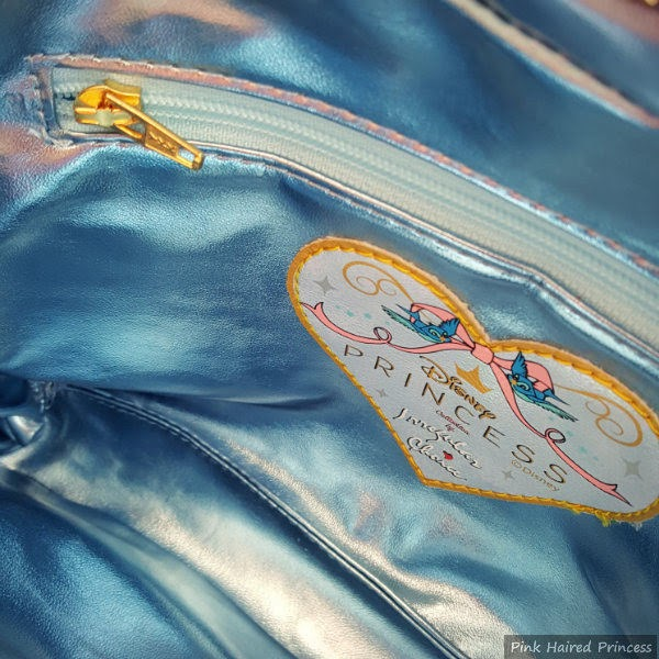 inside blue metallic lining of bag with zipped pocket