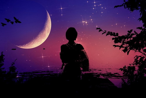 Silhueta de mulher observando a lua e as estrelas.