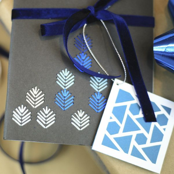 embroidered notebook cover and paper cut gift tag tied with blue velvet ribbon