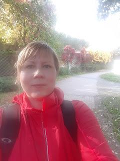 Postaajalla punainen takki, taustalla keltaisia ja punaisia lehtiä pensaissa