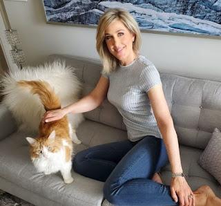 Anne Drewa sitting in a sofa with a cat