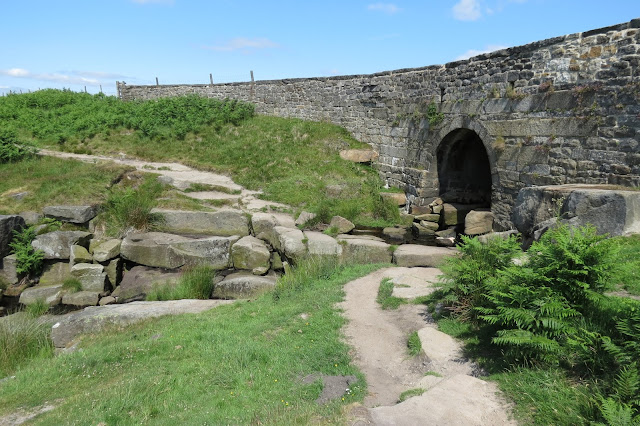 Looking at a stone bridge from below. An arch allows the brook to flow beneath the road from the moors above down into the valley.