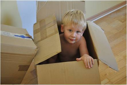 A kid playing with an empty box