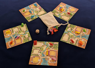 The five player boards, with some of the dinosaur meeples placed on them, and the bag of dinosaur meeples with the large wooden die.
