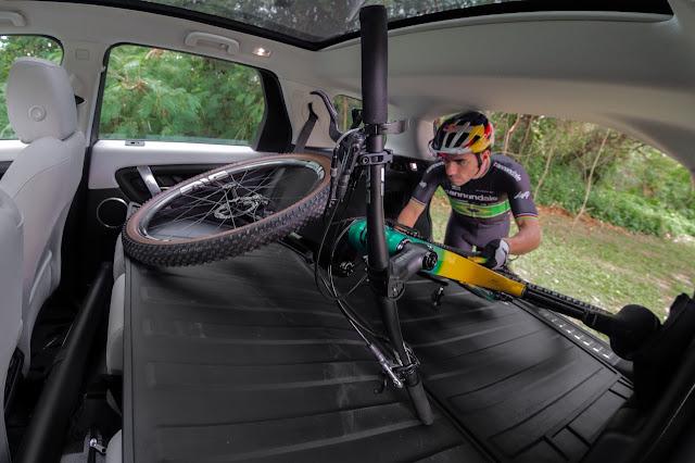 Henrique Avancini guardando a bicicleta na mala do carro Discovery Sports, da Land Rover