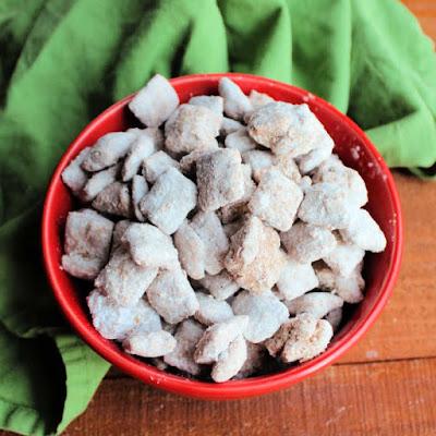 bowl of powder sugar coated muddy buddies ready to eat