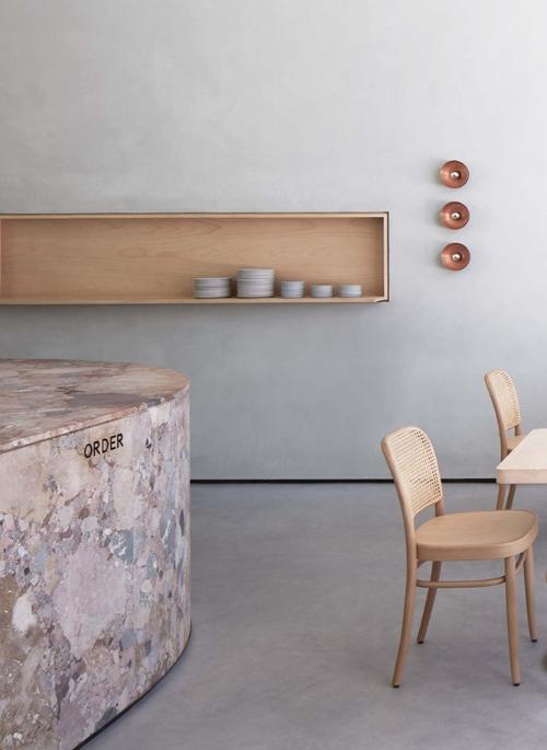 Café mit hellgrauen Wänden und hell Holzmöbeln