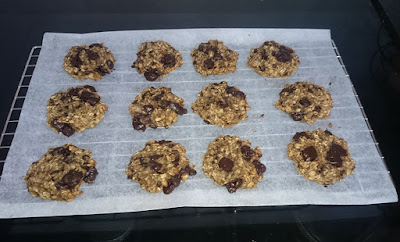 Banana, oat and chocolate chip cookies on a cooling rack.