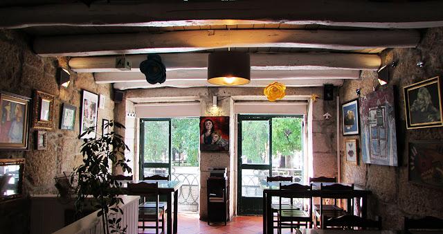 interior de um restaurante com mesas, cadeiras próximas das janelas e muitos quadros nas  paredes.