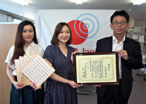 Ms. Tanaka(centre) and Ms. Chan(left) receive a certificate of appreciation from Mr. Horie (11 July 2020)